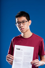 doubtful asian man holding a tax form