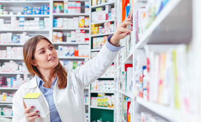 Photo of a professional pharmacist checking stock in an aisle of a local drugstore.