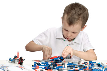 Young boy playing absorbedly with construction kit. With place for a text.