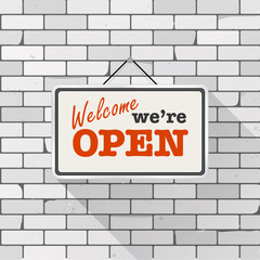 Simple white sign with text 'Come in we're open' hanging on a gray brick wall. Grunge brickwork background, textured rough surface. Creative business interior template for shop, store, supermarket.