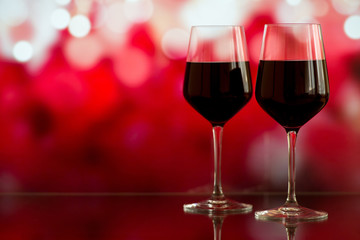 Two glasses of red wine against bokeh background with sparkles and roses. Very shallow depth of field. Selective focus, copy space