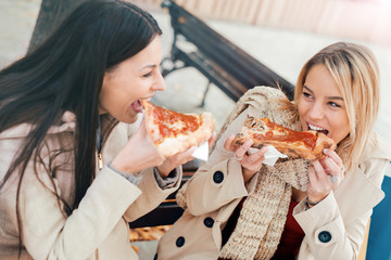 Friends eating pizza. Two young women eating pizza after shoppin