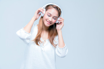 young girl wearing wireless headphones, listening a music