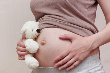 Pregnant woman belly with teddy bear