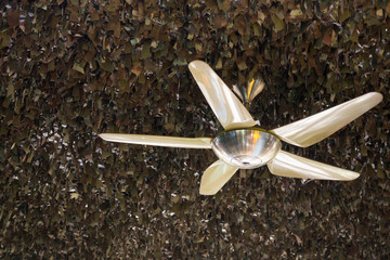 Vintage ceiling electric fan under camouflage fabric roof