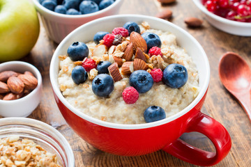 Oatmeal porridge loaded with fresh blueberries, raspberries, almonds and granola on red cup bowl. Healthy breakfast, diet food, healthy eating concept.