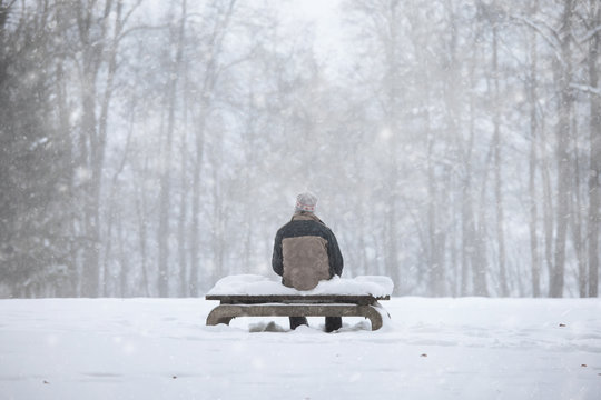 Lonely man sitting on the snowy benches in the park during the snowfall.
