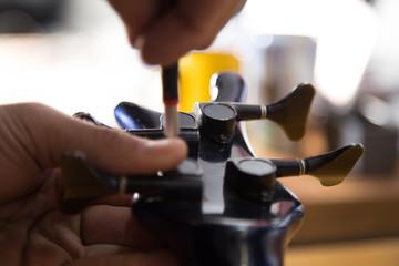 Lutnik w pracowni naprawia gitarę