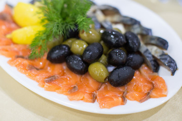 fresh roast wild pink salmon meat fillet with black olives and raw lemon