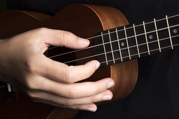 Somebody playing ukulele in close up view.