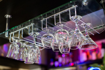 glasses in shelf above a bar rack