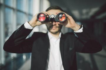 american businessman using binoculars in office