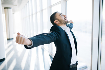 excited young caucasian businessman celebrate victory cheerful in modern office Wall mural