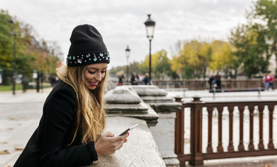 France, Paris, smiling young woman looking at cell phone