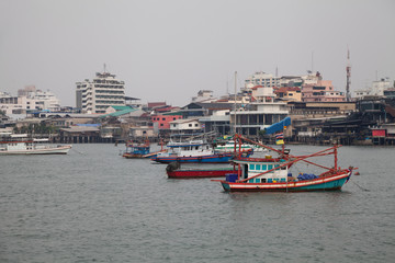 Old colorful fishing boats in a bay in Thailand on a cloudy day