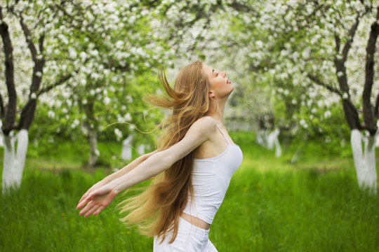 Beautiful woman jumps and flies in the blooming garden