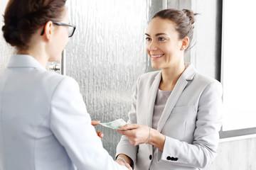 Wynagrodzenie za dobrze wykonaną pracę. Kobieta płaci pracownikowi.