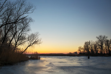 Winter landscape with sunset sky and frozen river.