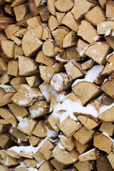 Chopped firewood logs in a pile with snow