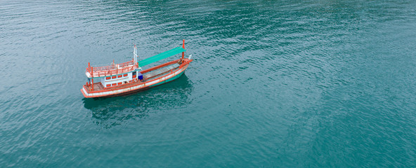 Aerial photo of colorful boat anchored in the sea bay with shallow clear green water
