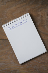 blank notepad on wooden table with phrase to do in 2017, space for your text