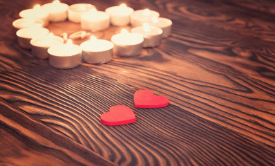 Two hearts, burning candles on wooden. Valentine's Day.