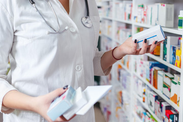 Woman pharmacist holding prescription checking medicine in pharmacy - drugstore.