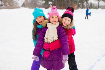 three attractive skater girl hug on the ice