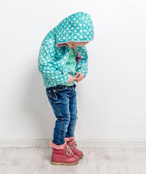 little girl fastening her blue jacket