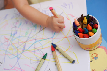 Hand of baby drawing lines on the white paper with colorful crayons. Focusing at the box of crayon and blur other part.