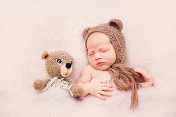 Новорожденный малыш в шапке с ушками с игрушкой спит на розовом пледе