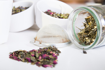 Green tea in jar and different kind of herbs on wooden table