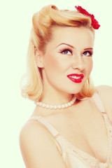 Vintage style portrait of young beautiful sexy girl with pin-up make-up and hairdo looking upwards