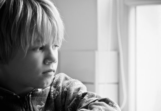 Little boy with a worried expression looks out of the window