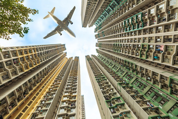 Tall city buildings in a crowded residential district of Kowloon, Hong Kong, and a plane flying over in the sky. Concept of transport, travel and business. View from bottom level.