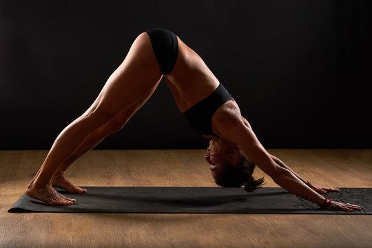 Yoga girl on fitness class background practicing yoga asana dog asana