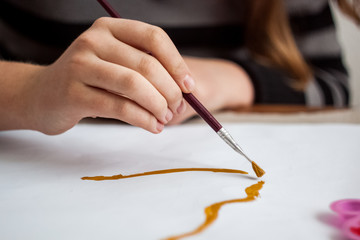 Girl painting with brush and colorful paint