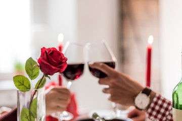 Young happy couple celebrating Valentine's day with a dinner at home drinking wine, cheers.
