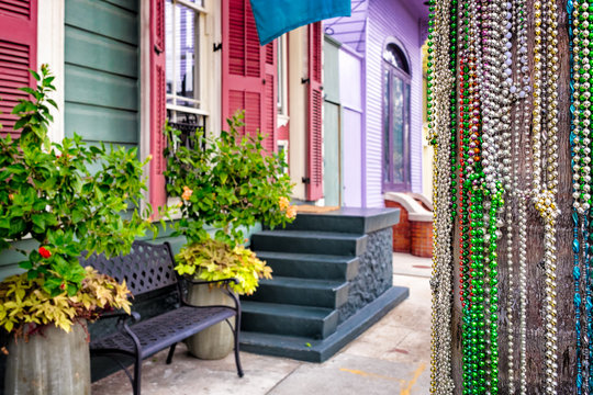 Mardi Gras beads decorate a telephone pole on a New Orleans street of colorful houses
