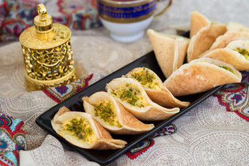 Traditional Arabic qatayef crepes stuffed with cream and pistachios, prepared for iftar in Ramadan on paisley background above
