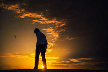 Silhouette of a man standing with a sad look on after sunset.