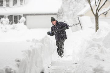 Man shoveling snow (shallow depth of field, focus on snow in for