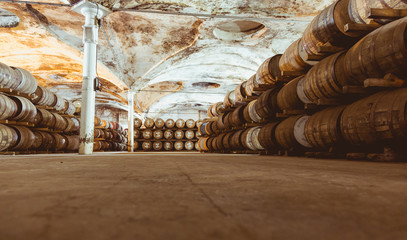 Old vintage whisky barrels filled of whiskey placed in order in
