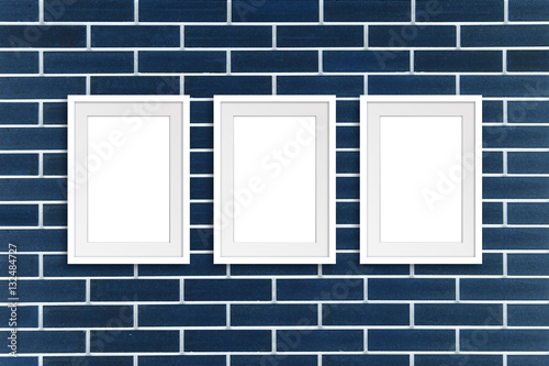 Three white frames on navy blue decorative bricks wall, Exhibition ...