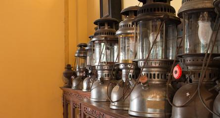 Group of old vintage storm lanterns, hurricane lamp put on vintage cabinet wood. Vintage lamp concept.