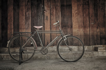 vintage bicycle leaning against wooden wall