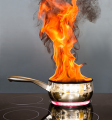 Saucepan on fire with flames