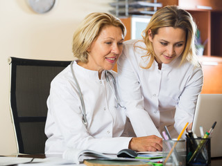 Elderly doctor consulting young female colleague
