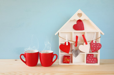 Wooden house with many hearts next to coffee cups