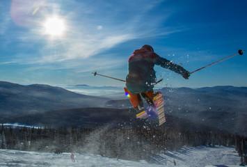 Skier on off-piste slope in forest riding very fast. Ski backcountry resort Sheregesh.